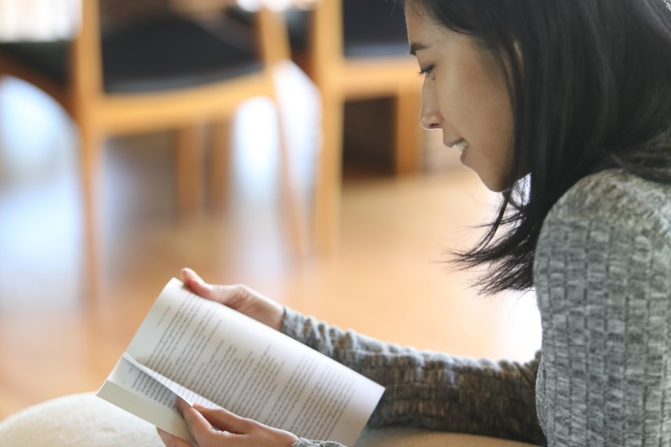 Young woman in a sweater smiling and reading the Immerse Bible