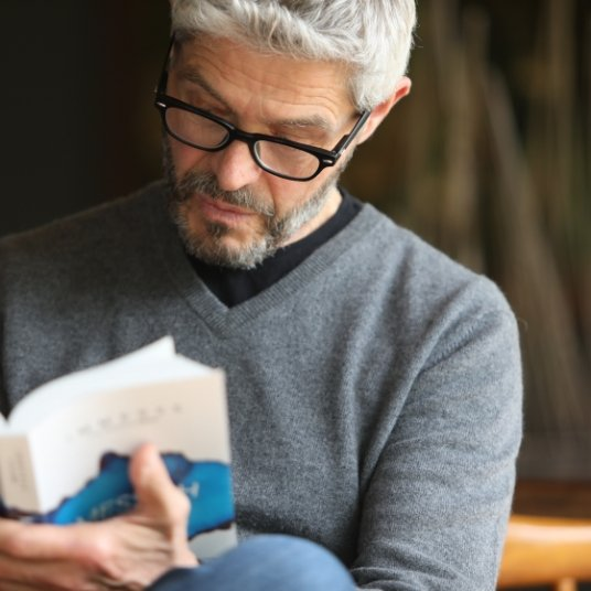 A middle aged man with glasses sitting cross-legged and reading Immerse: Messiah