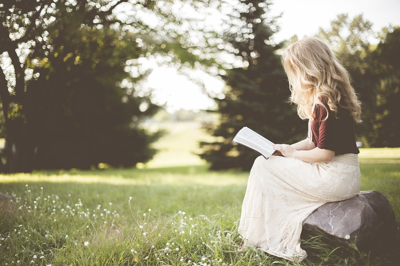 Pretty young blonde woman in profile sitting down and reading a book outside