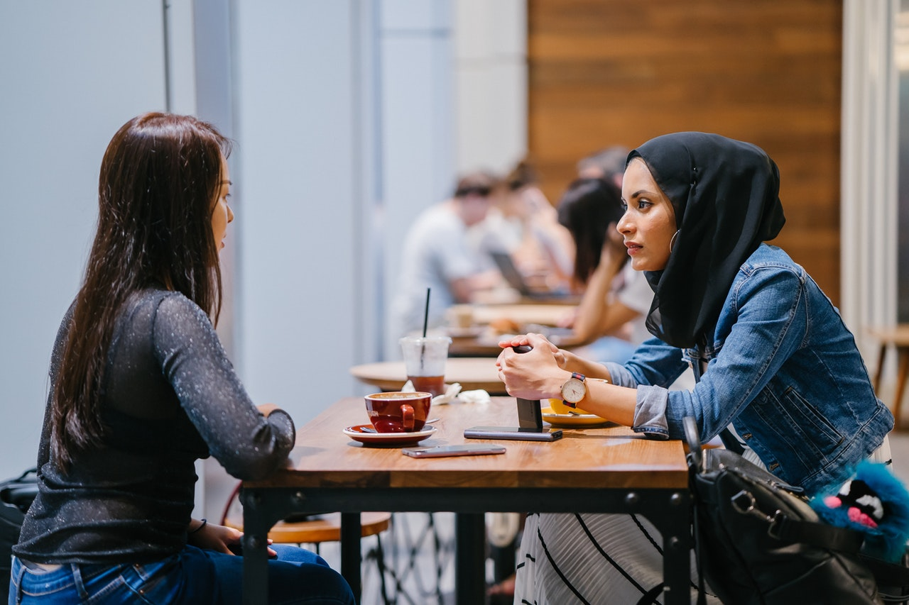 Young woman wearing burka sitting at table talking to another young woman with tea