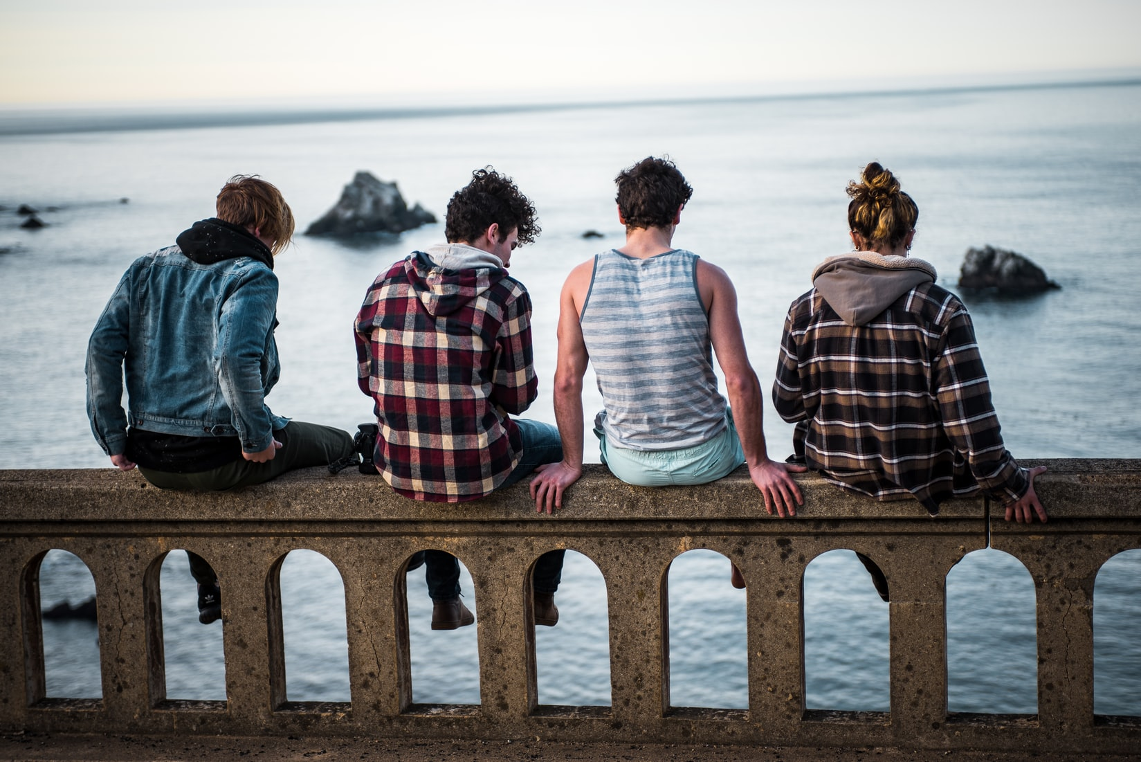 friends sitting by body of water