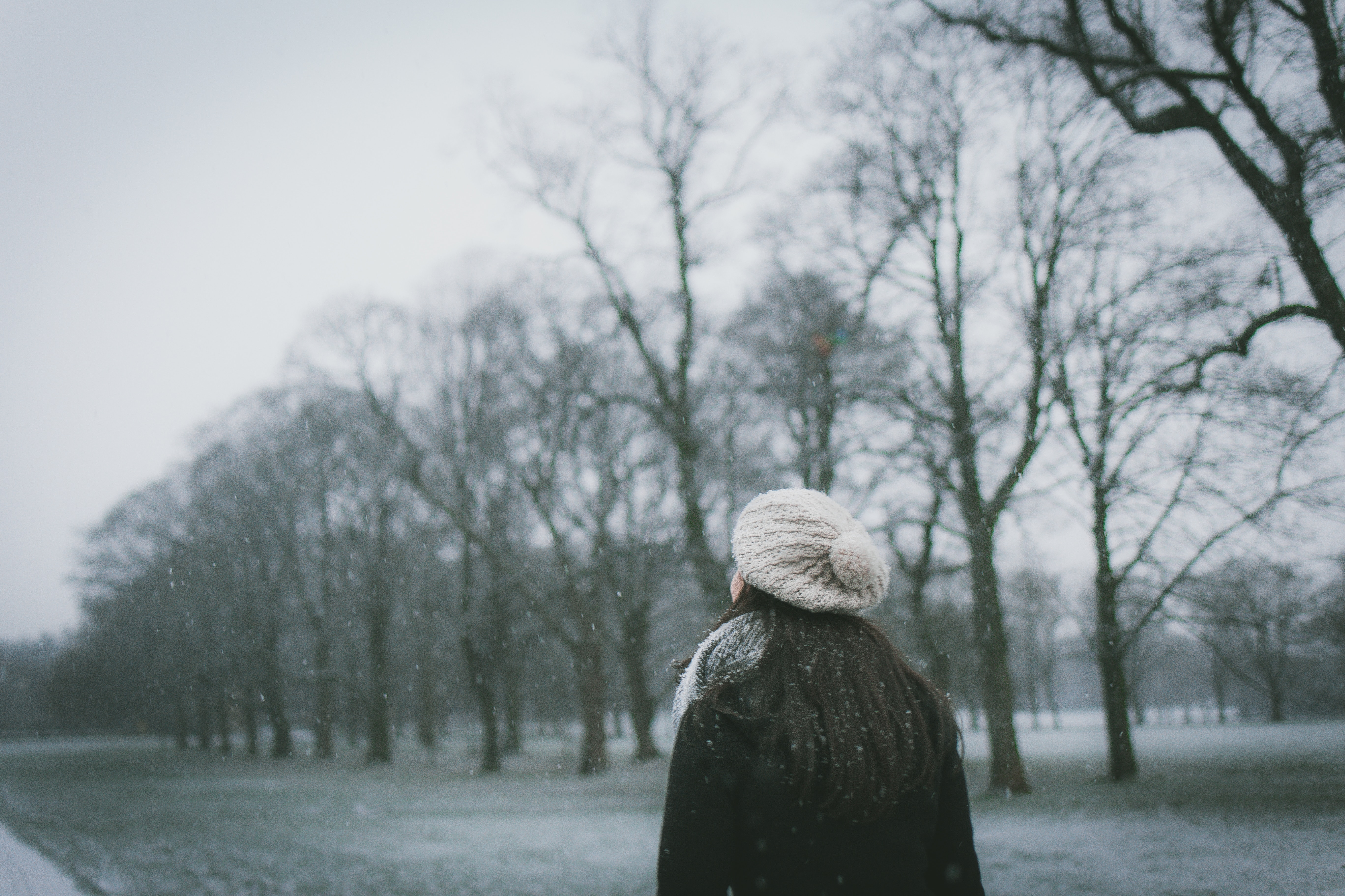 Young woman wearing black winter coat and white woolen hat looking up thoughtfully at gray sky with bare trees in background and snow falling.