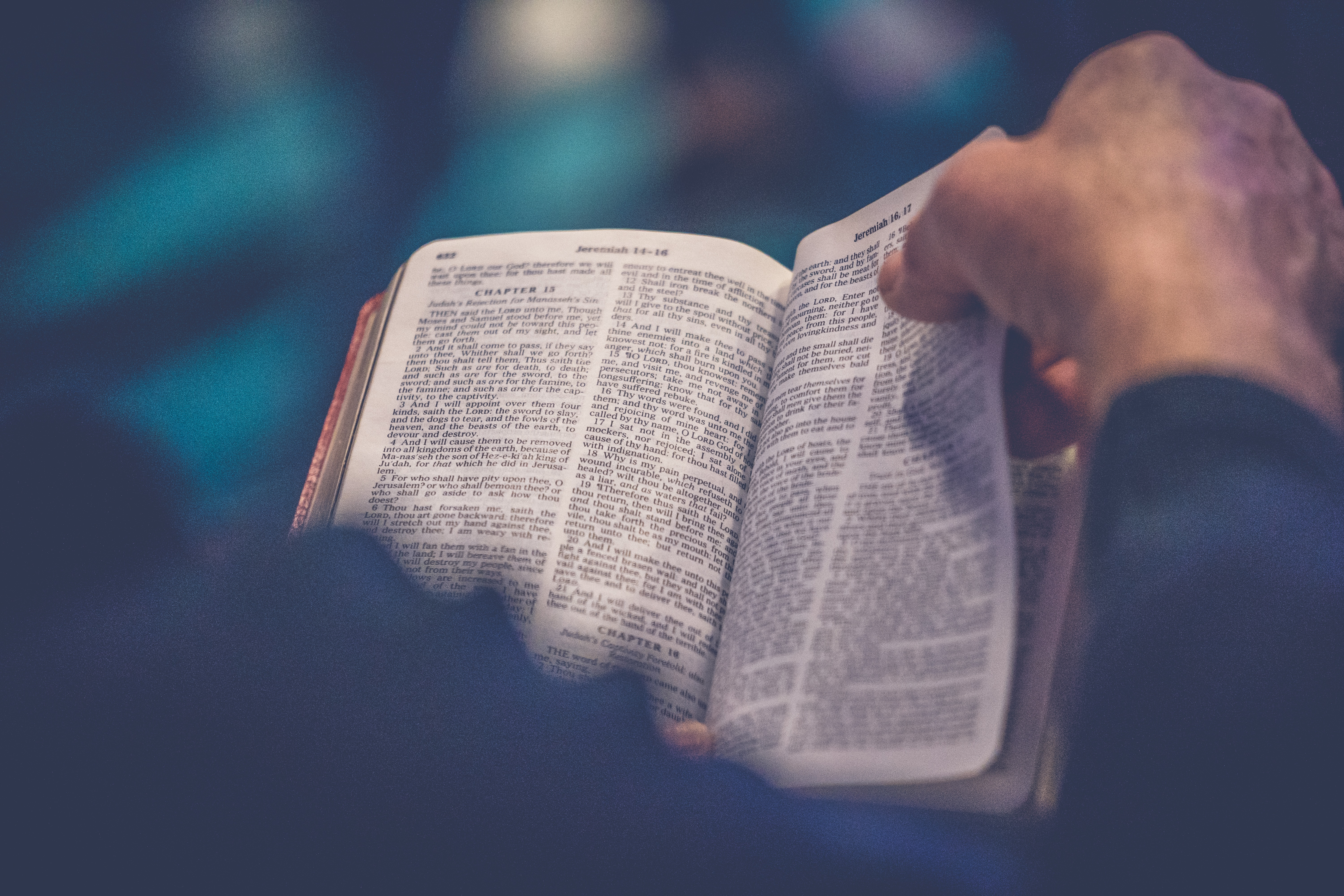 Close-up from behind of man's hand turning pages of Bible