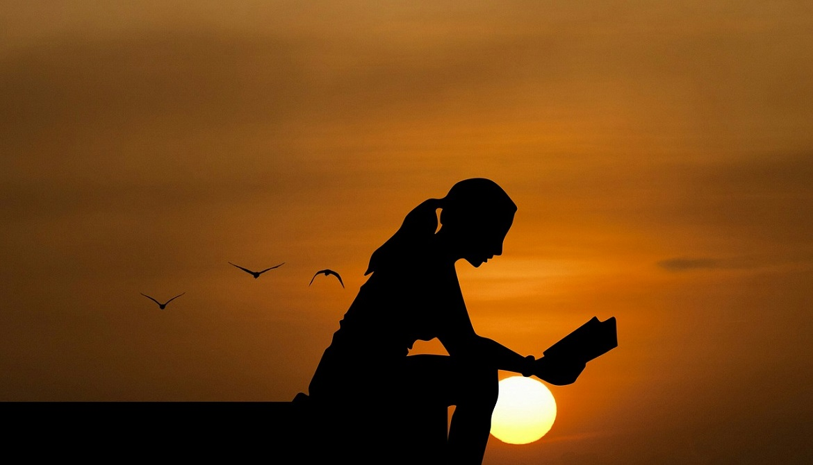 silhouette of young woman sitting and reading with setting sun in background
