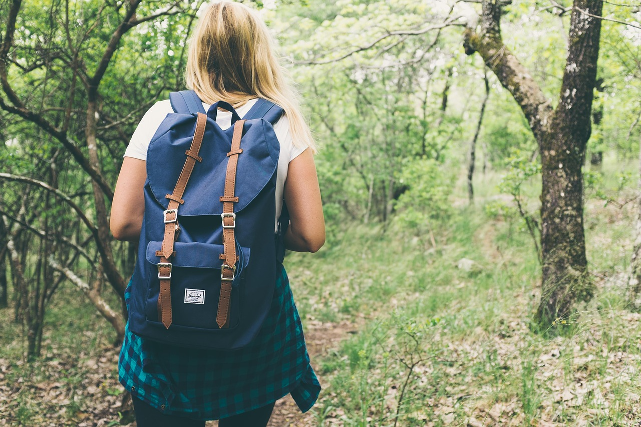 Young blonde woman walking down a wooded trail wearing short sleeves and a backpack