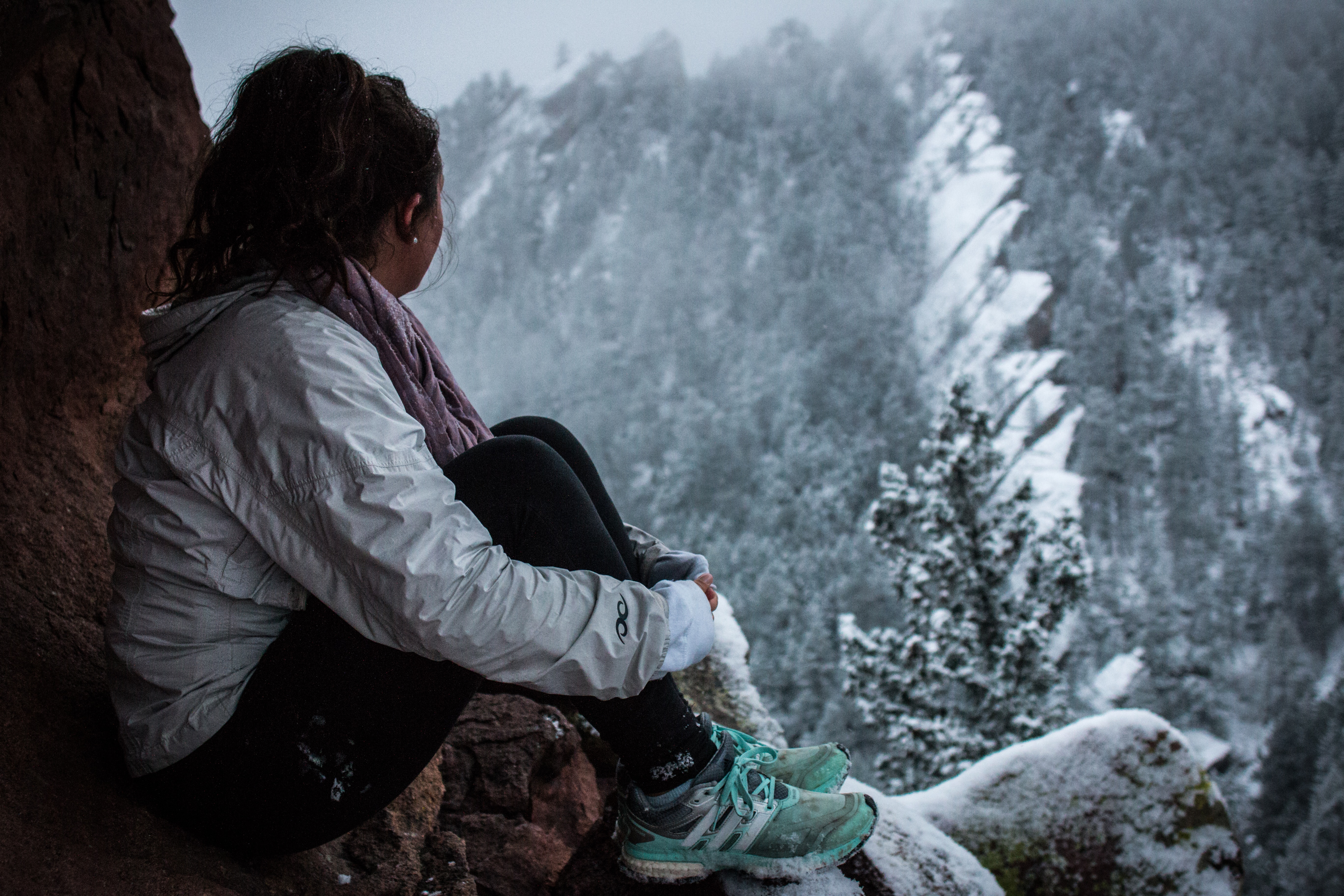 Young woman with dark hair wearing a winter coat and sneakers, looking out over a winter landscape
