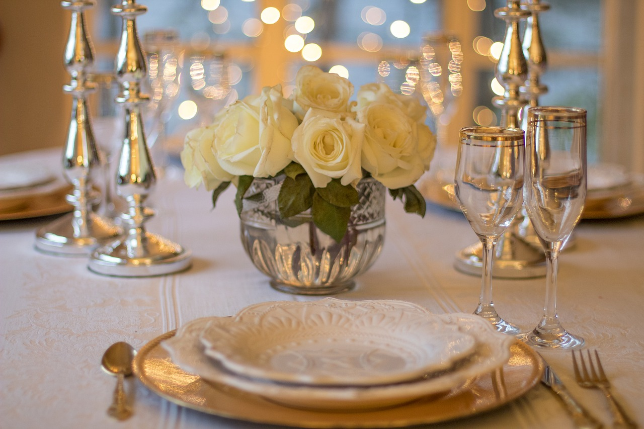 Elegantly set table with white tablecloth, fine china, silverware, silver candlesticks and lights in background, and a crystal vase of white roses