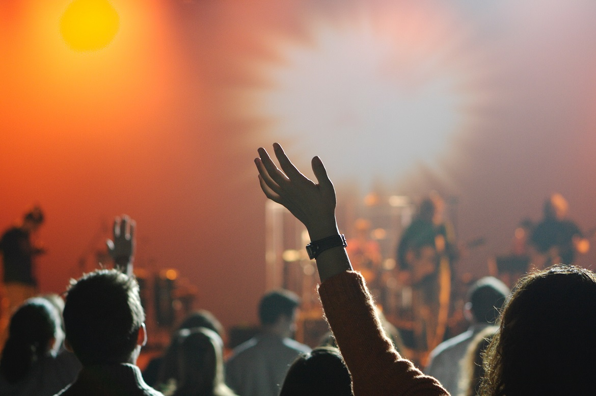 People raising hands at worship concert with warm, bright lighting in background and band on stage