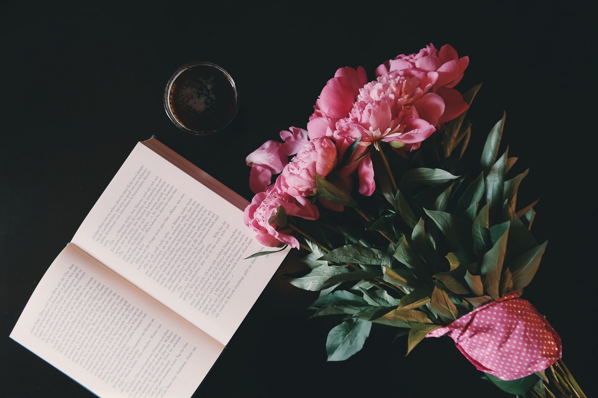 open book on dark wooden tabletop with bouquet of pink carnations