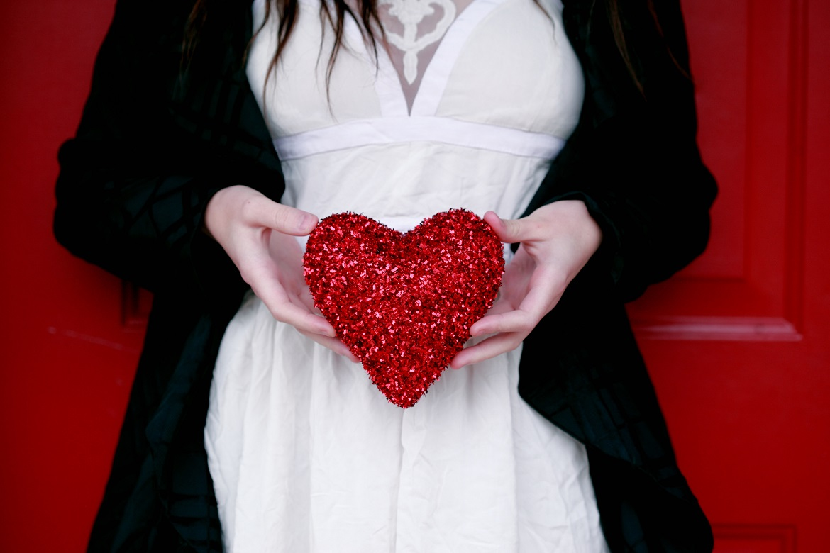 Young woman wearing a white dress with black sweater standing against red door holding sparkly red Valentine's heart