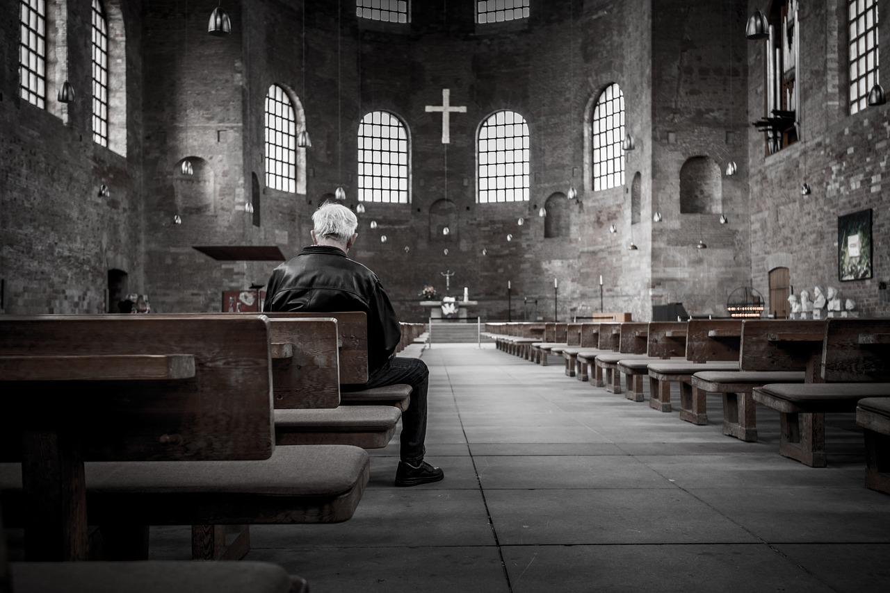 Elderly white-haired man sitting in pew inside a dark gray church