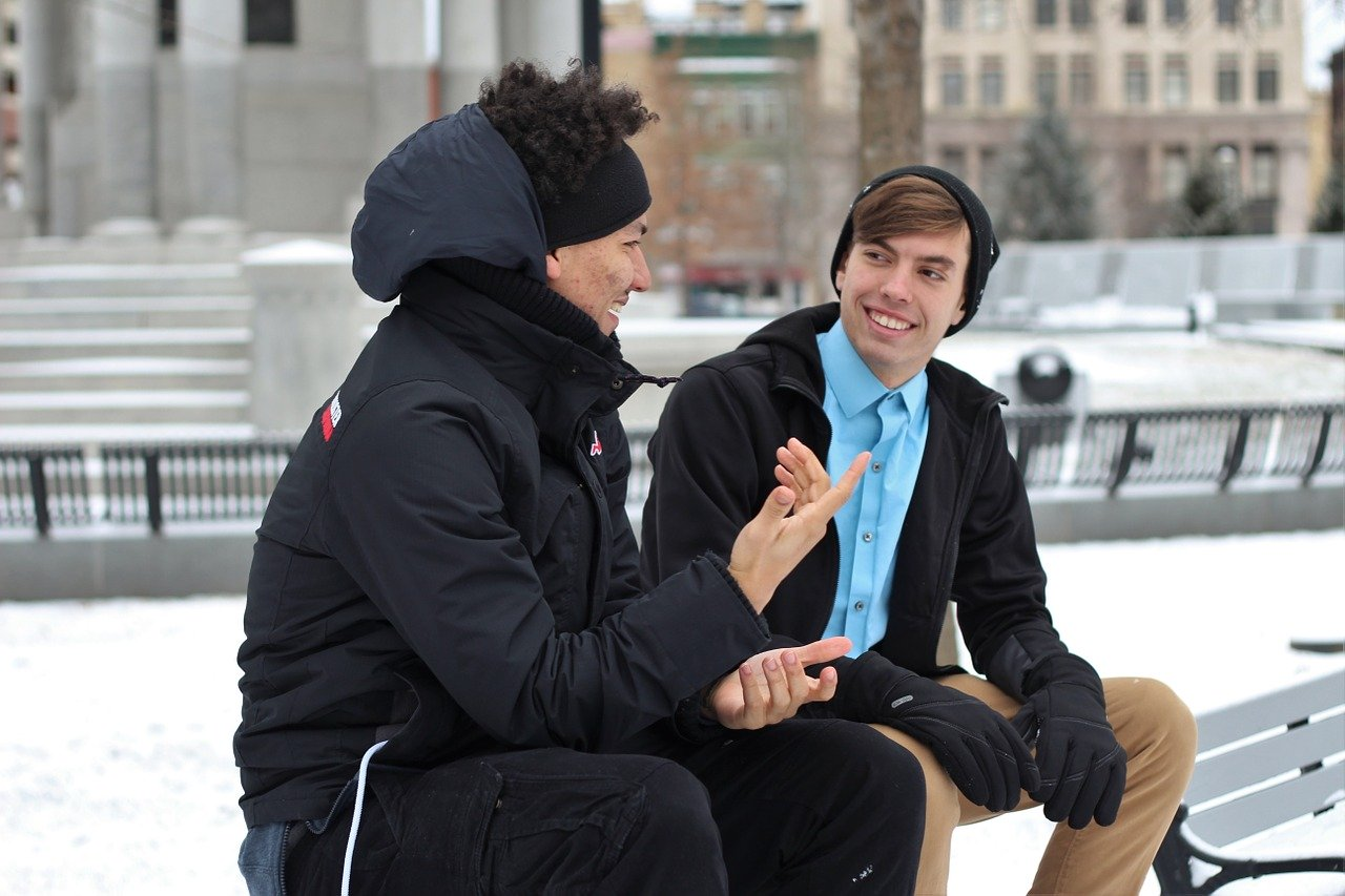 two young men wearing winter coats and hats sitting on a bench outside talking and smiling