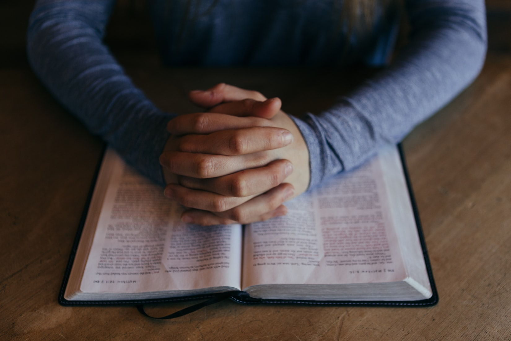 person praying with hands folded across bible