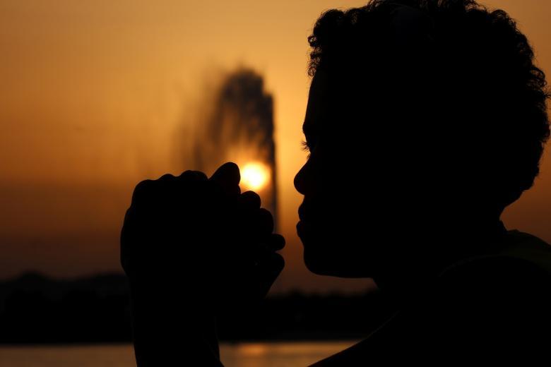 woman praying outside during nighttime