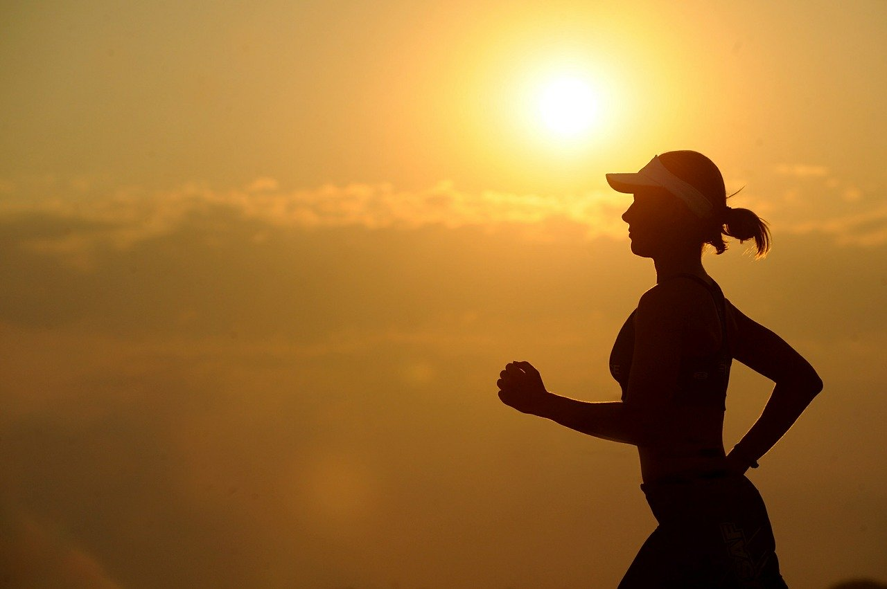 Silhouette of young woman jogging wearing a visor with setting sun in background