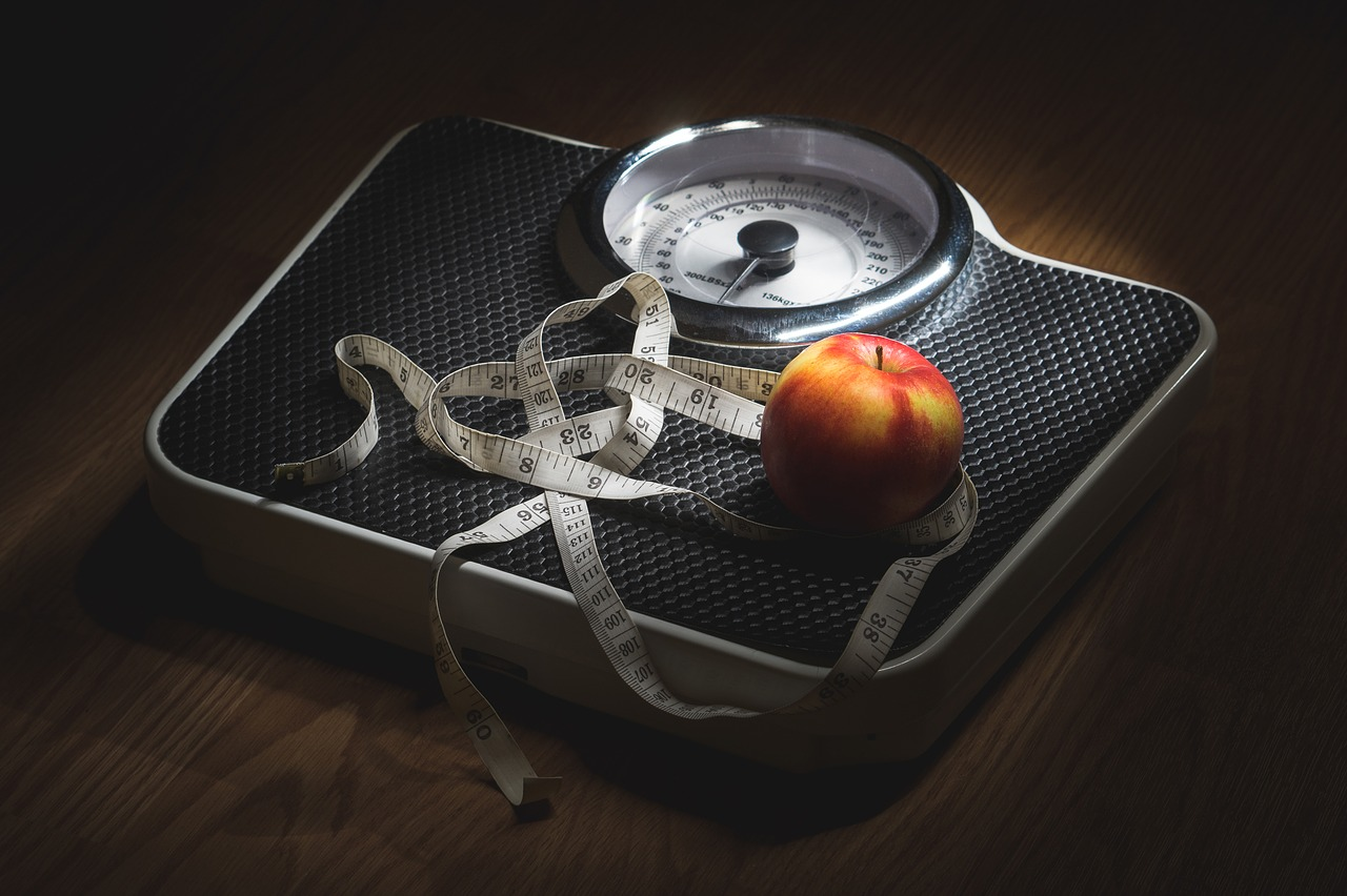 Black bathroom scale on dark wooden floor with red apple and tape measure for weight loss