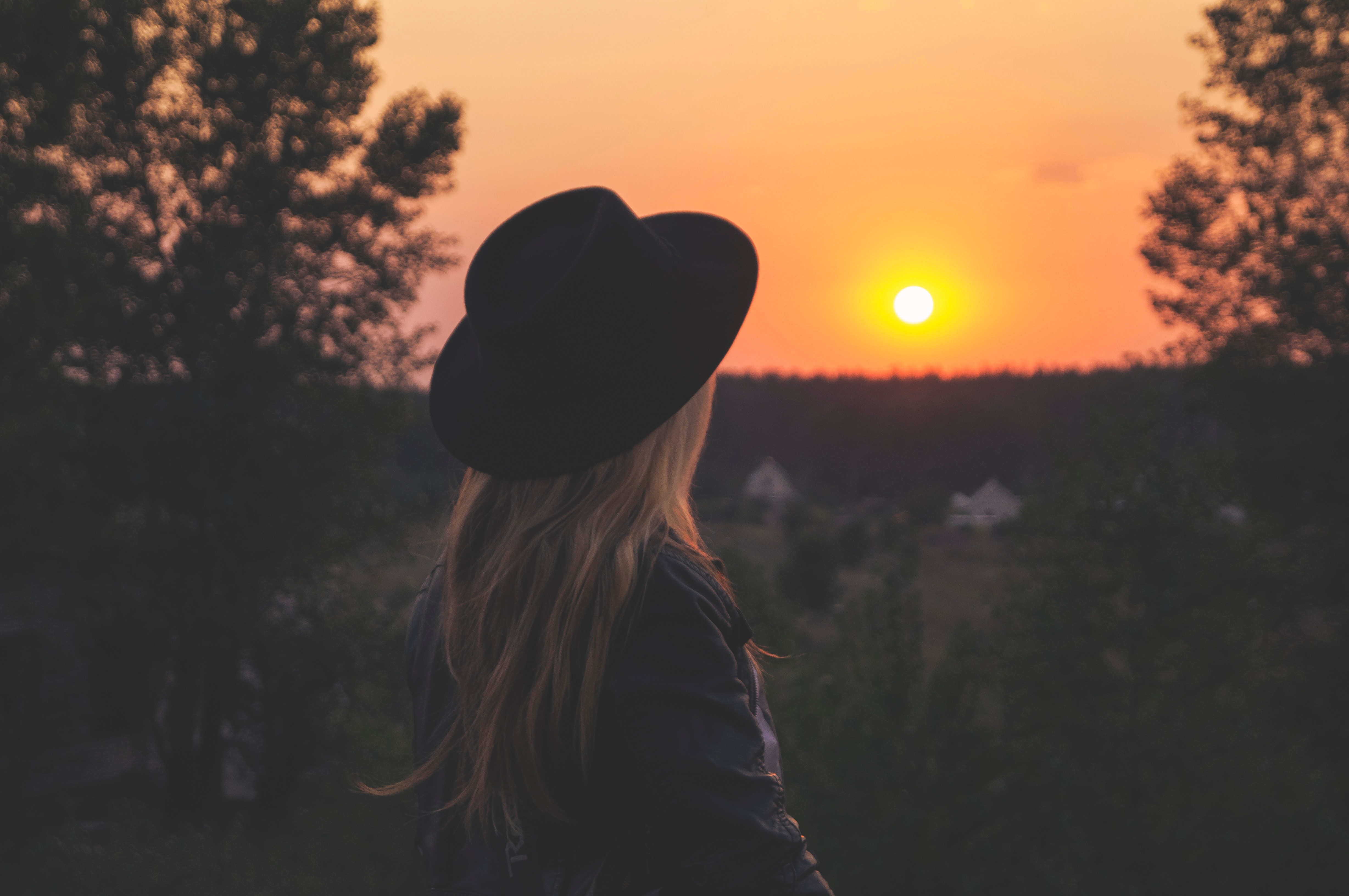 young blonde woman wearing black hat facing setting sun on horizon