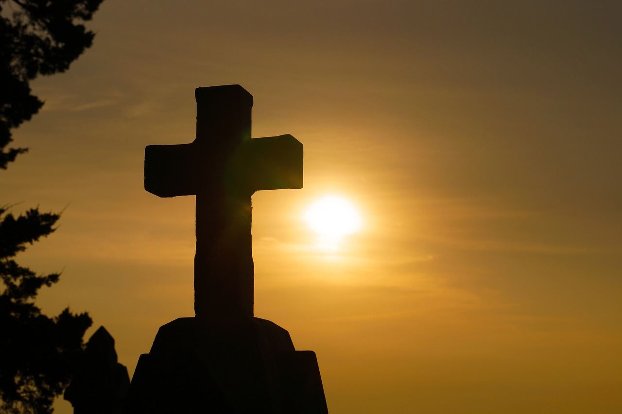 silhouette of large stone cross against hazy sunset sky