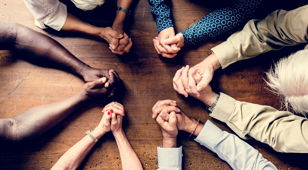 Birds-eye view of small group of diverse people with hands folded on a tabletop in prayer