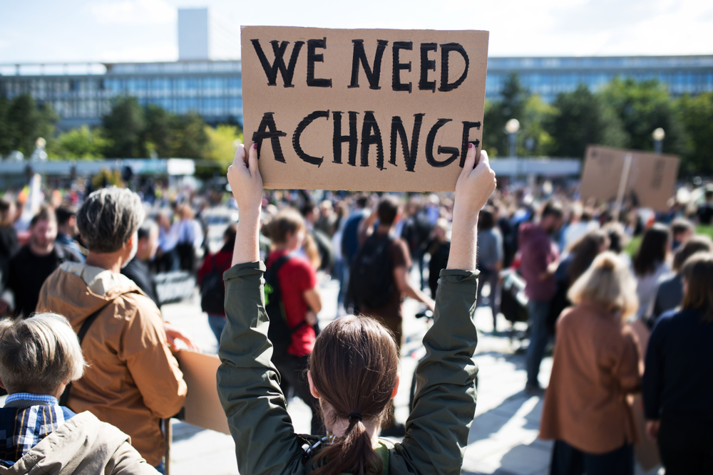 """crowd of people protesting outside with young white woman holding a cardboard sign saying """"we need a change"""""""