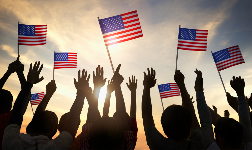 Silhouette of small crowd of people waving American flags in the sunset