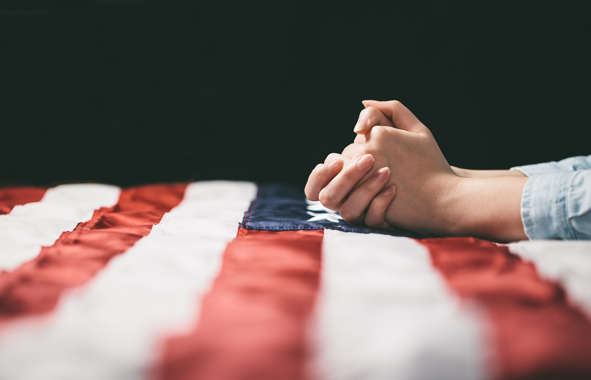 Close-up of hands folded in prayer on American flag