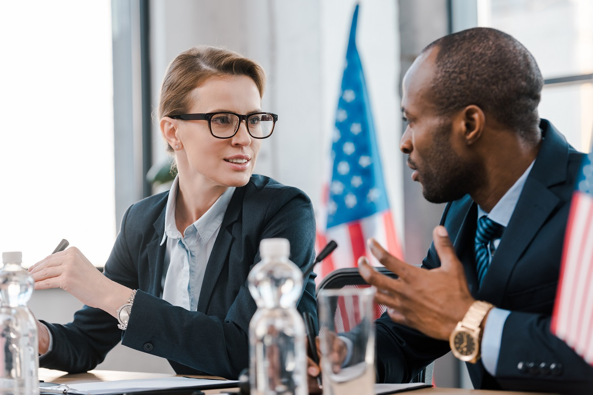 Black male and white female government officials talking cordially at a meeting with American flag in background