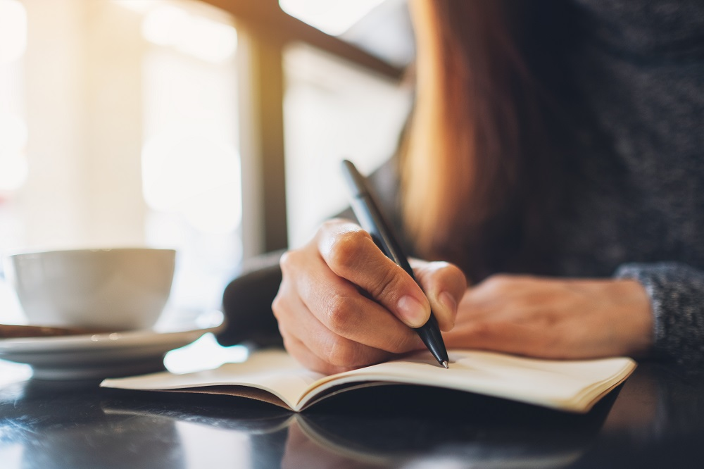 Close-up of young woman writing in a notebook with a cup of coffee on the table