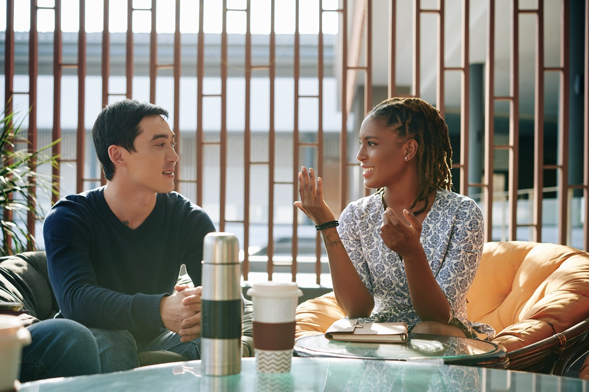 Smiling young black woman talking with young Asian man in an indoor cafe