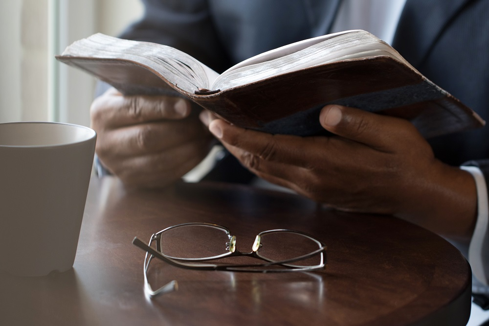 Close-up of black man reading book or Bible with white mug and eyeglasses on table