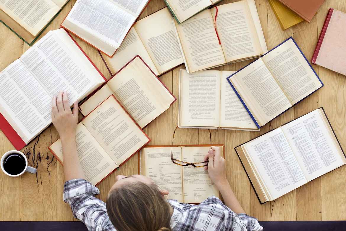 birds-eye view of young blond woman with open books spread out on a wooden tabletop