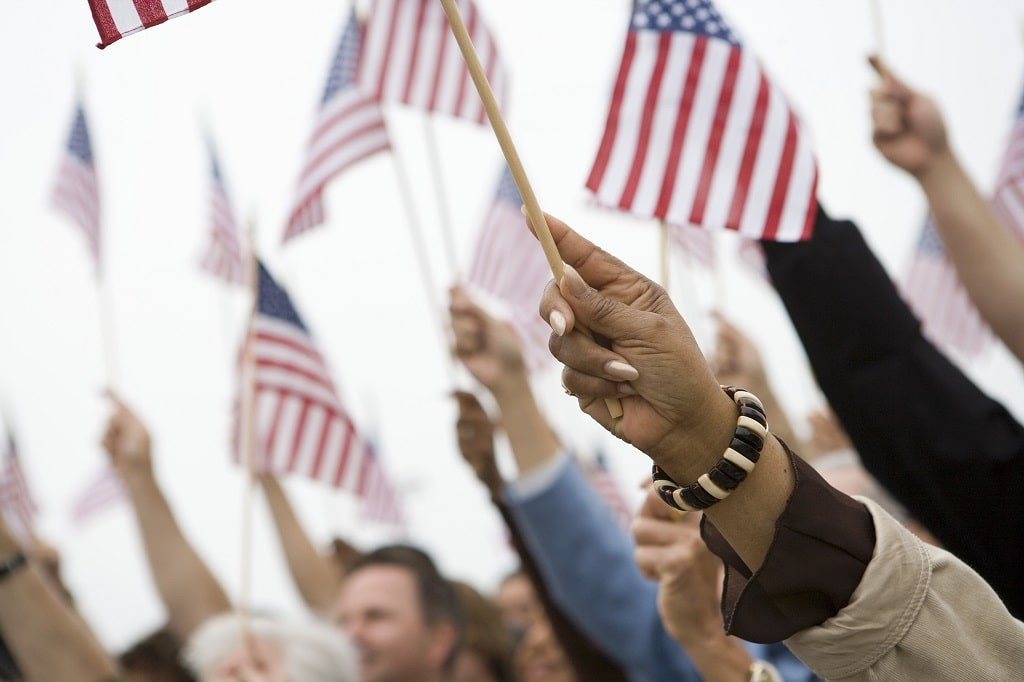 Americans of various races raising hands holding American flags