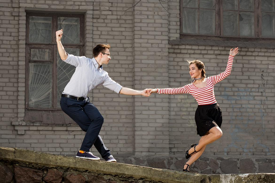 happy young couple swing dancing outside building