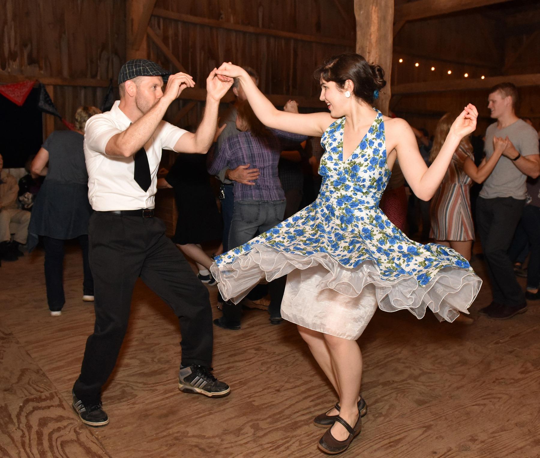 happy couple swing dancing wearing vintage clothing