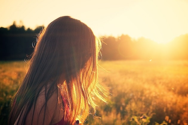 Girl in a field at sunset, her face is unseen. Talk about your testimony.