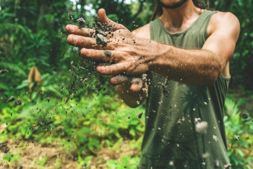 A man wipes his hands of dirt, showing he has worked hard, demonstrating God's love for us all