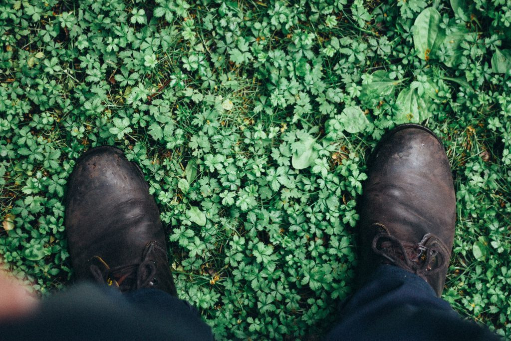 A man's boots stood on green grass, indicating he has come home to God's Love