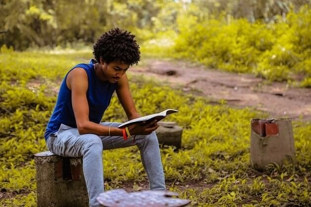 Young man sat on a log in a park, reading. Encouraging quiet time.