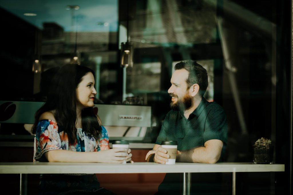 Male and female couple talk about faith in a cafe, seen through a large window.