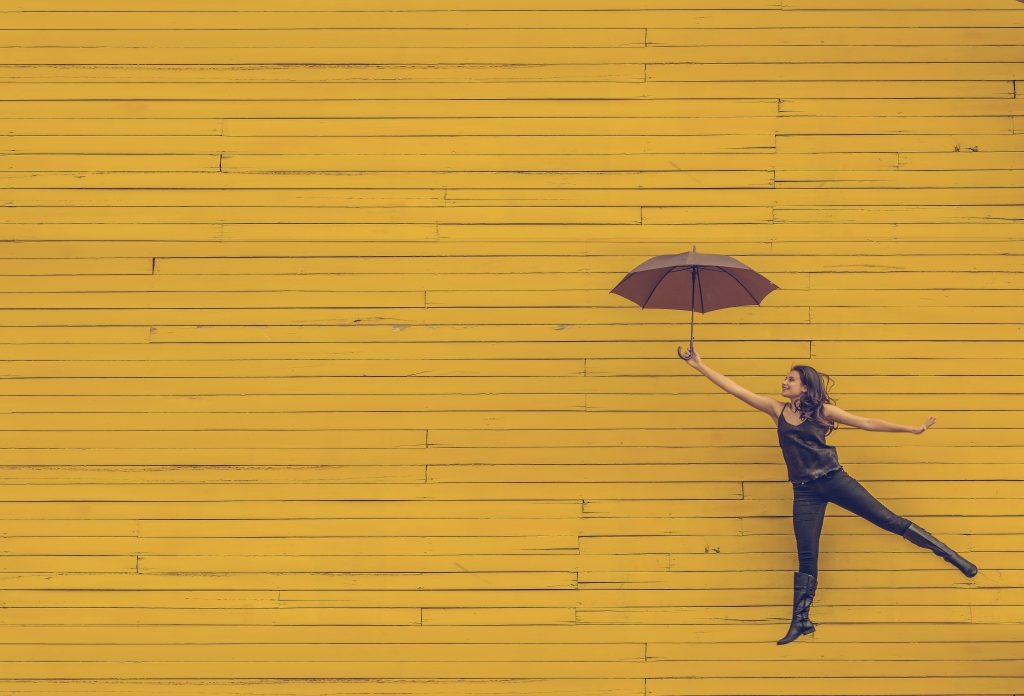 Woman jumping for joy with an open umbrella, in front of a yellow wall. best devotionals for new believers, 60 days to Happiness devotional.