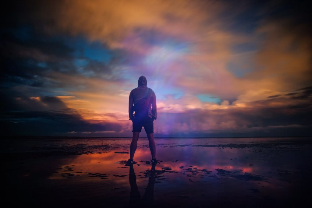 God offers hope in all situations, especially when forgiving our sin. A young man stands on a wet beach with a moody, colorful sky reflected on the still water.