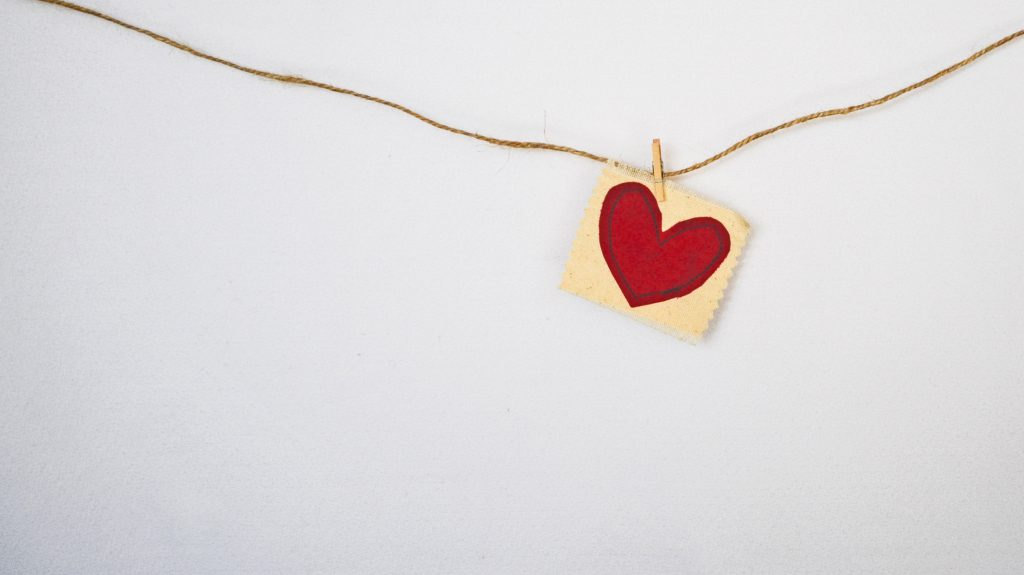 Paper heart pinned to a string across a white wall. Think about your testimony and how you would tell it to others.