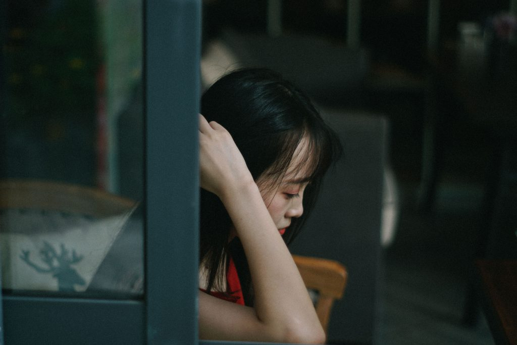 A young Asian woman looks down towards the floor in a moody shot. Thinking about how she might be strong enough to stop sinning.