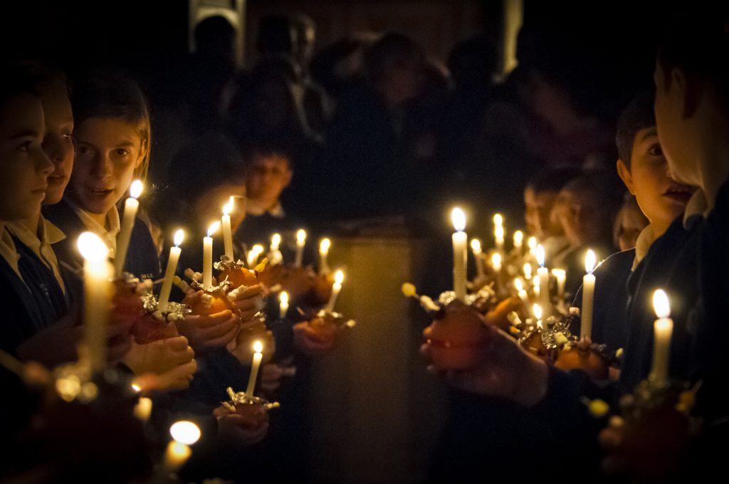 An image of rows of children holdings candles at a Christmas church service.