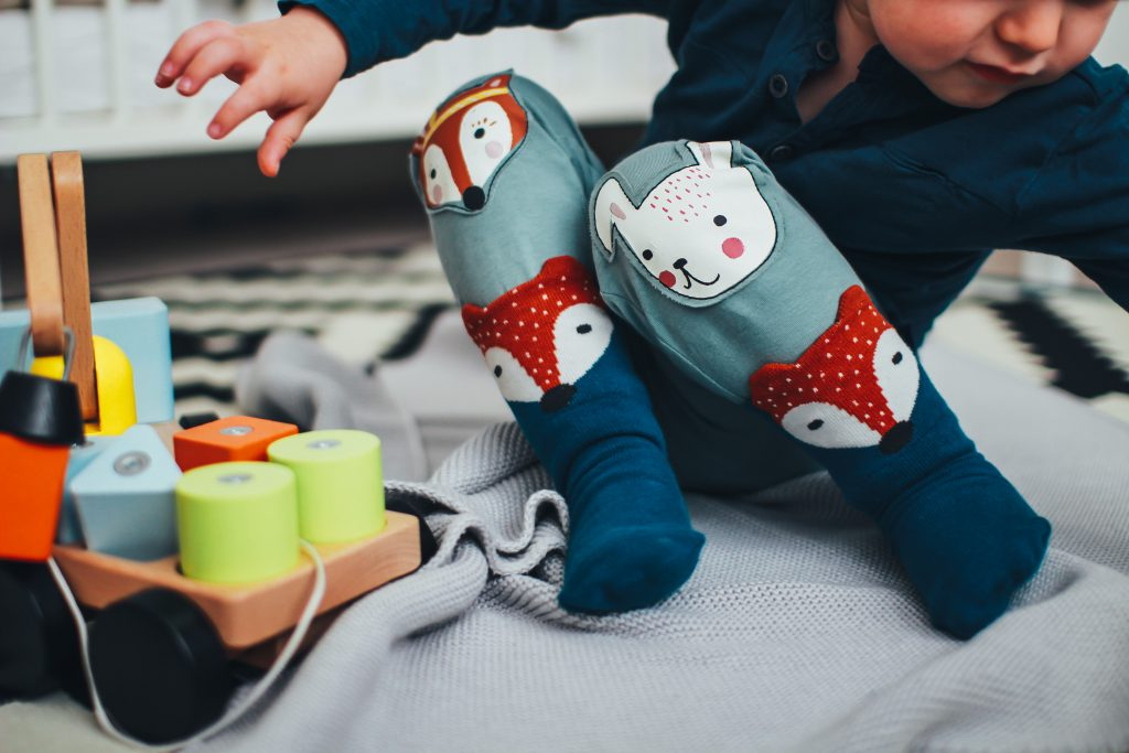 A young child in colorful stockings sits on a blanket and plays alongside a wooden toy with blocks in various shapes. Children should be taught about giving, as Jesus gave to us, as well as receiving at Christmas.