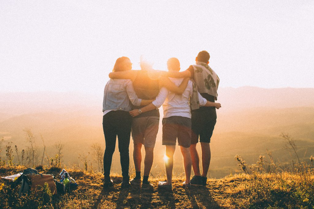 Four small group friends stand together on top of a hill, watching the sunset.