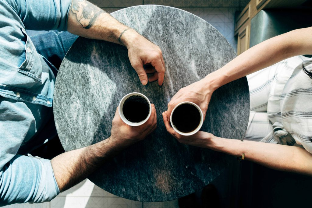 An older man and a younger woman meet for coffee and to talk about their spiritual lives, an example of mentorship.