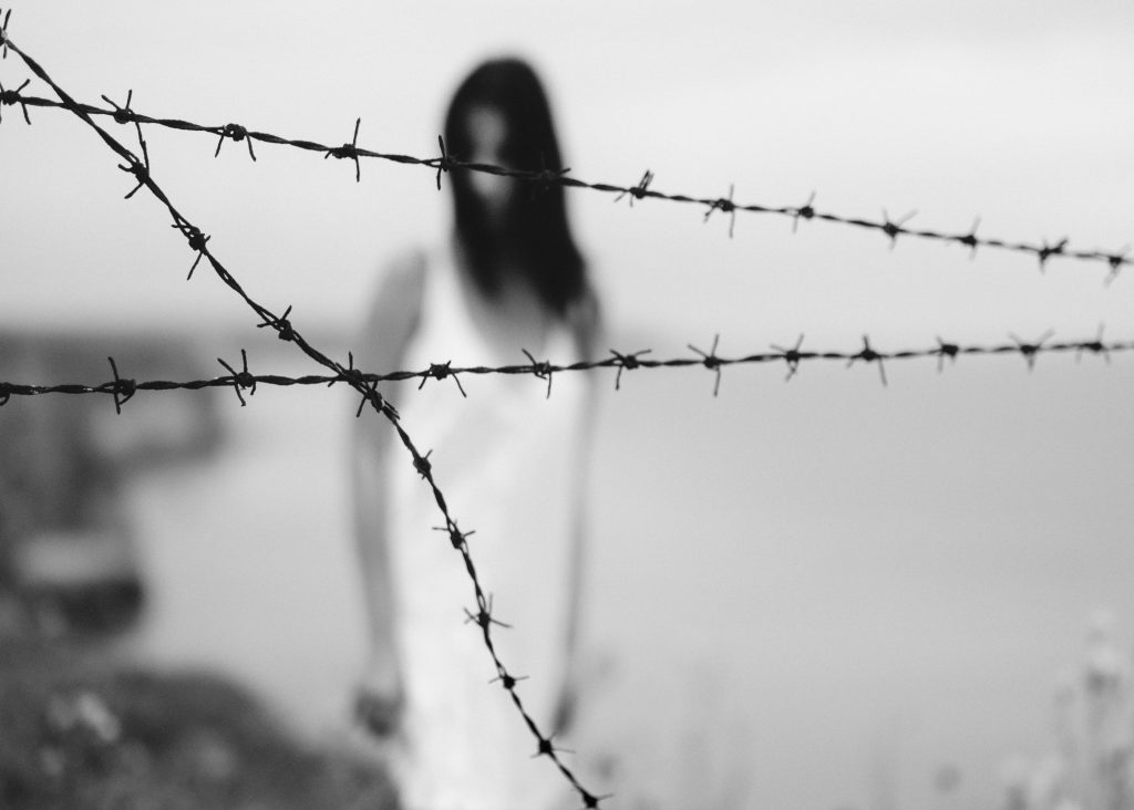 Why does God allow suffering in the world? Image of a woman behind barbed wire, black and white.