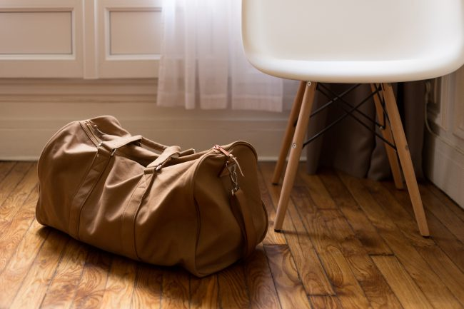 A packed duffel bag sits on a wood floor next to a white and natural wood chair. Forgiveness can be very difficult to achieve, but we are called by God himself to do it.