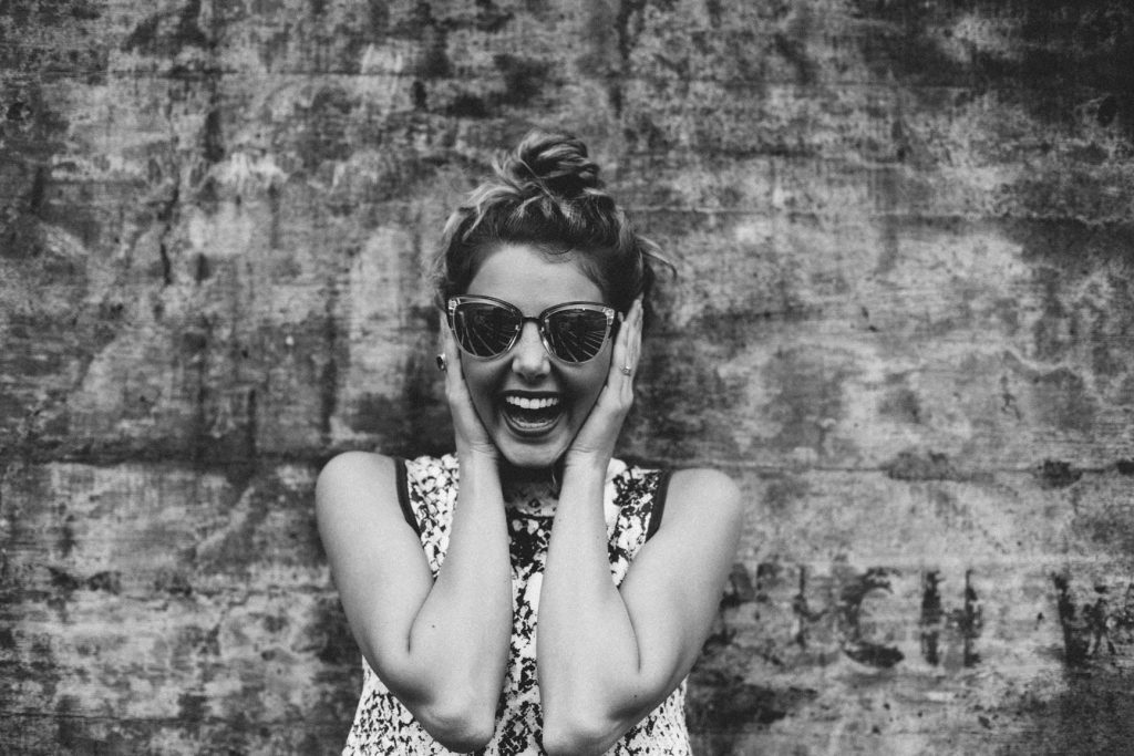 A young woman in sunglasses laughs with glee as she shares her own story.